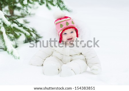 Beautiful laughing baby girl sitting under a Christmas tree wearing a white snow jacket and warm knitted hat - stock photo