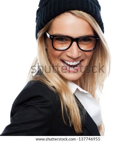 Beautiful laughing blond woman in a fashionable black cap and jacket wearing glasses, sideways head and shoulder portrait looking at the camera - stock photo