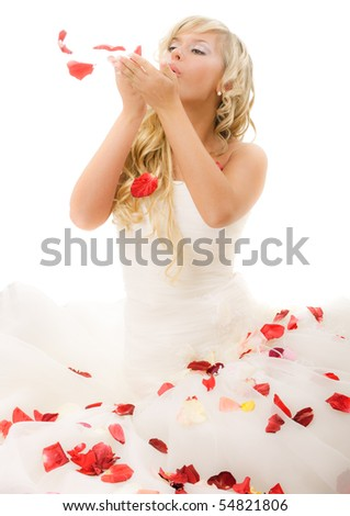 Beautiful laughing bride. She blows on petals of roses.