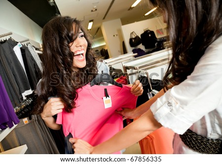 Beautiful laughing females looking at blouse in fashion store - stock photo