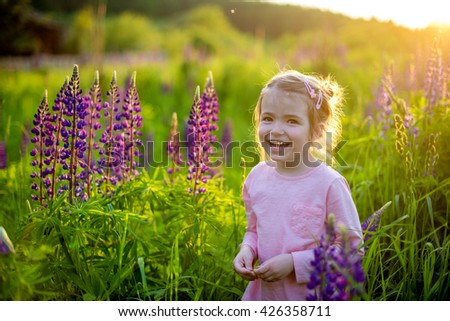 Beautiful laughing girl in a field of purple lupine flowers on sunset - stock photo
