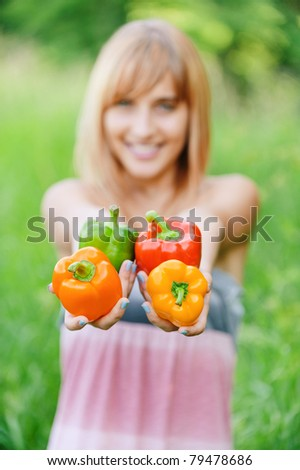 Beautiful laughing girl with sweet pepper, on green summer background. - stock photo