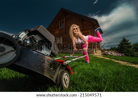 Beautiful laughing housemaid with lawn mower near country house.  - stock photo