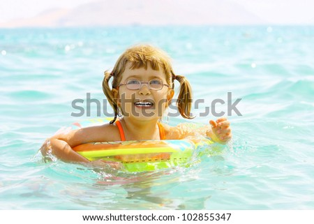 Beautiful laughing little girl 3 years old floats in the sea on inflatable wheel