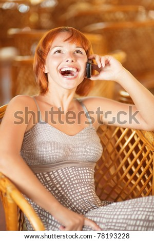Beautiful laughing woman talks by mobile phone. - stock photo