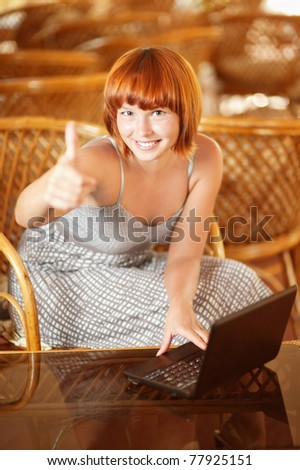 Beautiful laughing woman with laptop lifts thumb upwards meaning that all perfectly. - stock photo