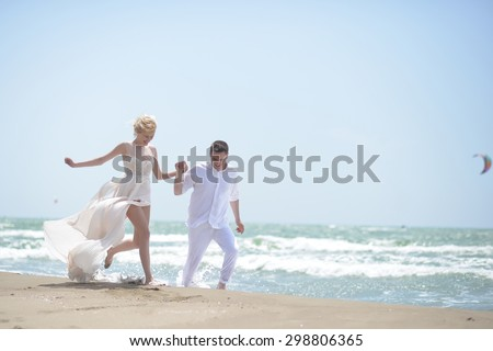 Beautiful laughing young wedding couple of man and woman in white running along ocean beach shore on windy weather sunny day outdoor on blue sky background, horizontal picture - stock photo