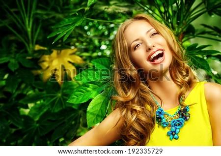 Beautiful laughing young woman among the tropical plants. Vacation. Tropics. Fashion shot. - stock photo
