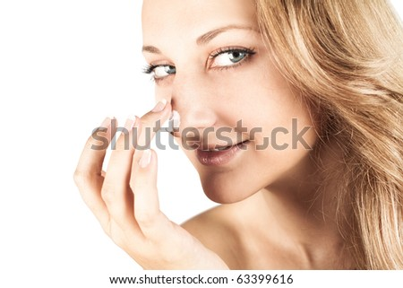 Beautiful laughing young woman with facial cream on her nose - isolated on white - stock photo