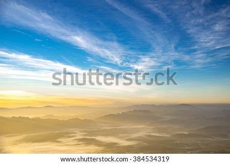 Beautiful layers of mountain range landscape with winter blue sky from top view in majestic sunrise and fog - stock photo