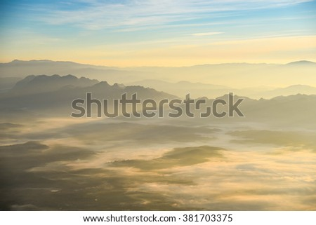Beautiful layers of mountain range landscape with winter sky from top view in majestic sunrise and fog - can use for background in natural concept - stock photo