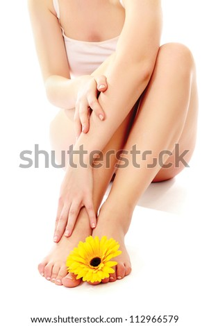 Beautiful legs and feet with flower, isolated on white background - stock photo