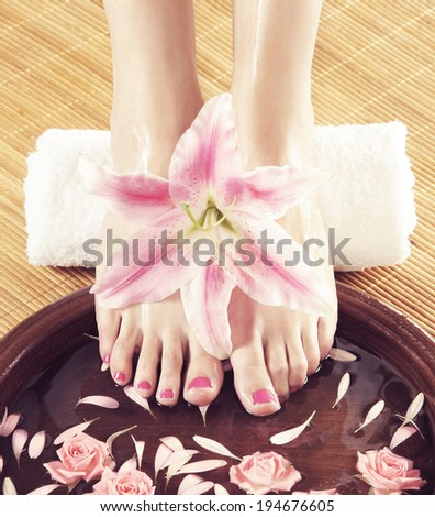 Beautiful legs, flowers, petals and ceramic bowl. Summer spa background. - stock photo