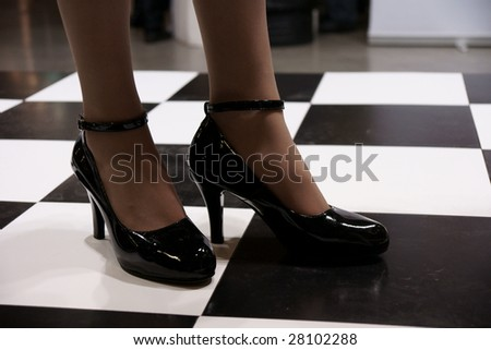 beautiful legs in black patent-leather shoes on chess-checked floor - stock photo