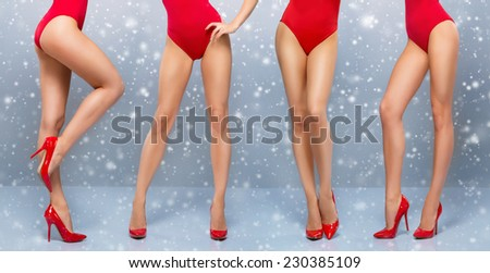 Beautiful legs of young and sporty woman in red swimsuit over the Christmas background with a snowflakes - stock photo