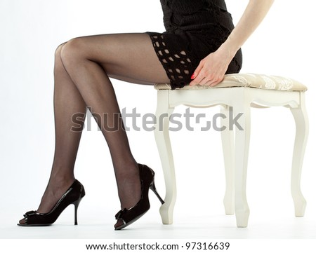 Beautiful legs of young woman sitting on banquette holding red handbag; white background - stock photo