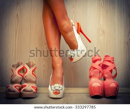 Beautiful legs. Woman trying many shoes. choosing. - stock photo