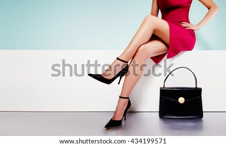 Beautiful legs woman wearing red dress with black purse hand bag with high heels shoes sitting on the white bench.  with copyspace. - stock photo