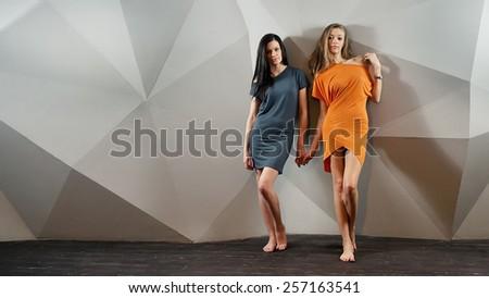 Beautiful lesbian flirting couple in the studio. - stock photo