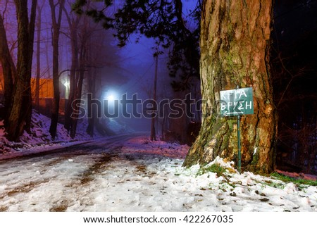 "Beautiful light and shadows disappearing in distant road with trees and sign labeled ""Cold Spring"", winter scene in Greece - stock photo"