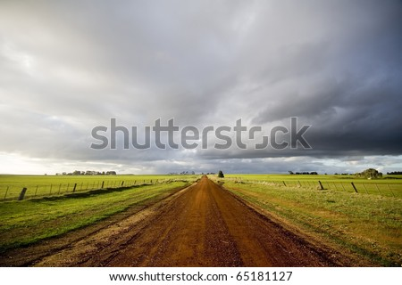 Beautiful light appears amidst winter storms on a deserted country road.