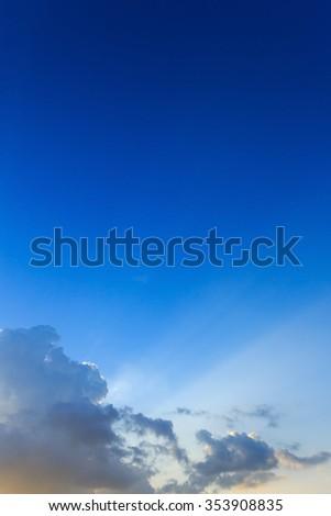 beautiful light of sunbeams through clouds, light rays on dramatic sunset sky background - stock photo