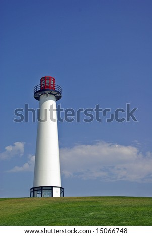 Beautiful Lighthouse Standing Atop Grassy Hill - stock photo