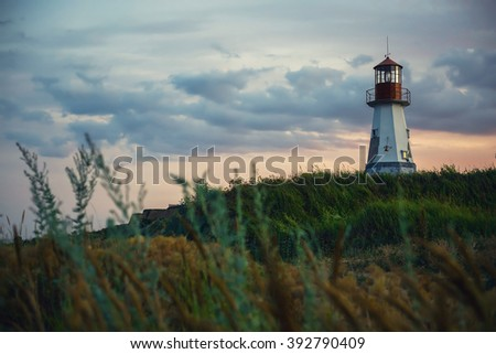 Beautiful lighthouse standing on a hill above the sea