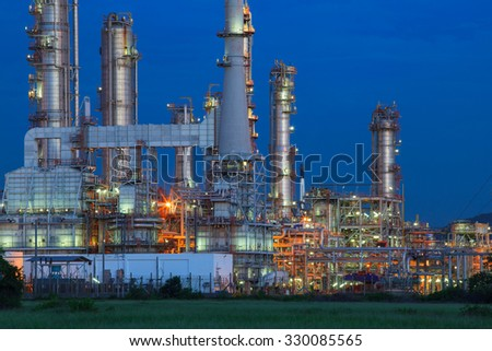 beautiful lighting of oil refinery palnt against dusky blue sky of oil refinery plant in heavy petrochemical industry estate  - stock photo