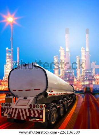 beautiful lighting of oil refinery plant in heavy petrochemical industry and container truck transportation of petroleum - stock photo