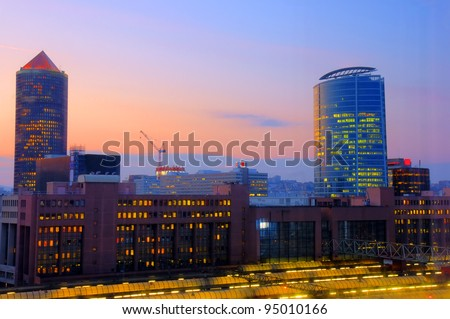 Beautiful lights of a sunset over a modern area of an old city with train TGV station in the foreground, Lyon, France. - stock photo