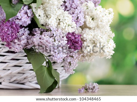 beautiful lilac flowers in basket on wooden table on green background - stock photo
