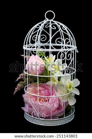 Beautiful lilac flowers in decorative cell, on black background - stock photo