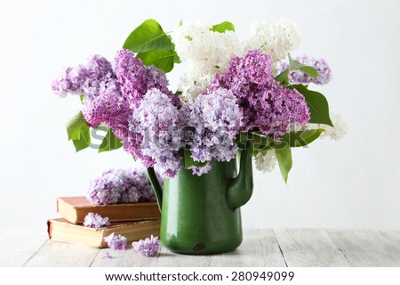 Beautiful lilac in pitcher on white wooden background - stock photo