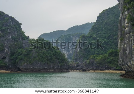 Beautiful limestone mountain scenery with beach at Ha Long Bay, North Vietnam. Cloudy winter weather