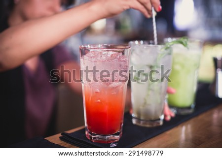 Beautiful line of red and different colored alcohol mojito cocktails with mint on a open air party, tequila, martini, vodka, and others on decorated catering bouquet table on open air event party  - stock photo