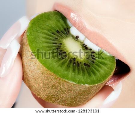 Beautiful lips and delicious kiwi - stock photo