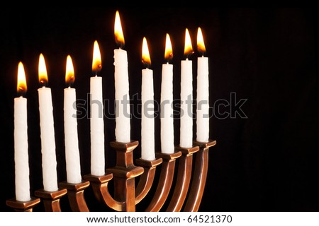 Beautiful lit hanukkah menorah on black background. - stock photo