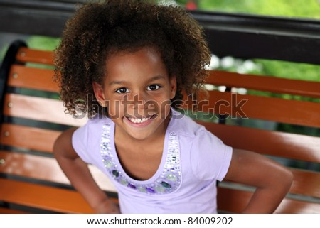 beautiful little african-american girl seated in natural light - stock photo