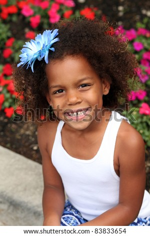 beautiful little african-american girl with flower in hair - stock photo