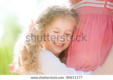beautiful little and happy daughter hugging her mother. Nature background.