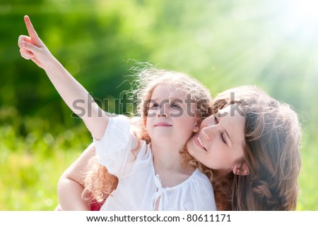 beautiful little and happy girl pointing up with her hand, showing something to her mother. Summer park in background. - stock photo