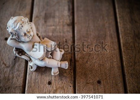 Beautiful little angel statue. Detail and portrait of lie down cupid. - stock photo