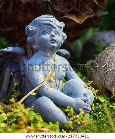 Beautiful little angel statue in garden. Detail and portrait of sitting cupid. - stock photo