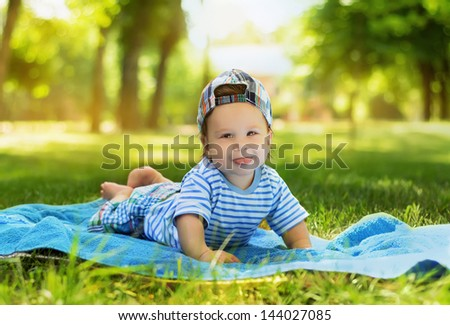 Beautiful little baby boy lying on the mat on the grass in the park - stock photo