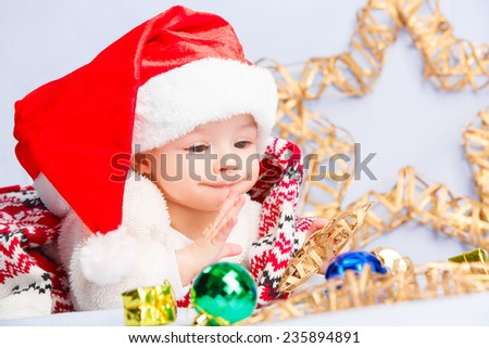 Beautiful little baby celebrates Christmas. New Year's holidays. Baby in a Christmas costume and in santa hat - stock photo