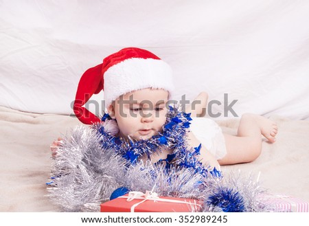 Beautiful little baby celebrates Christmas. New Year's holidays. Baby in Santa hat - stock photo