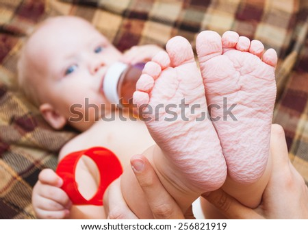 beautiful little baby drinking tea or juice from bottle. focus on feet. several  months old child. eating, food and drinks concept.  close up of cute feet wrinkled after bath. family concept - stock photo
