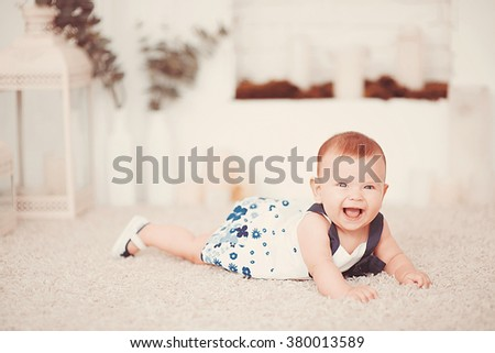 Beautiful little baby girl lies on a light carpet in the room - stock photo