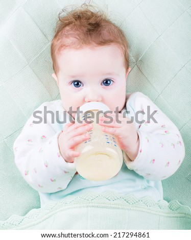 Beautiful little baby with a milk bottle under a warm knitted bl - stock photo